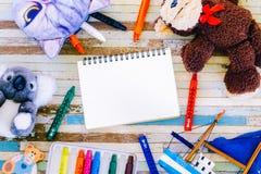 Kredki, zabawki, śliczne lale z pustym miejscem otwierają notatnika o i kredkę Zdjęcie Stock