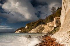 Kredowe falezy z niebieskim niebem i chmurami w świetle słonecznym z lasem w tle obraz stock
