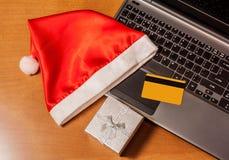 Kredytowa karta, laptop, prezenta pudełko i Santa kapeluszowy odgórny widok na drewnianym tle, Obraz Stock