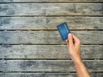 Kredytowej karty ręka trzyma dalej drewnianego stół Obrazy Royalty Free