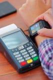 Kredytowej karty zapłaty śmiertelnie obsiadanie na drewnianej powierzchni, ręka jest ubranym mądrze zegarek z ekranem zaświecając Obrazy Stock