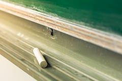 Kreide, die allein in Tray Below Green Board Education schreibt zu liegt Stockfotos