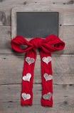 Kreidebrett für Mitteilung mit Rot strickte Bogen und Herzen Stockfotos