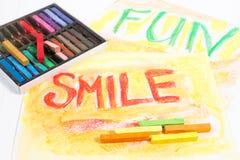 Kreidepastelle mit Wörtern Lächeln und Spaß Stockfoto
