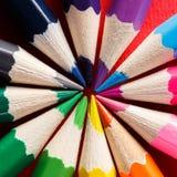 Kreis bildete sich durch farbige Bleistifte auf dem roten Hintergrund Stockfotografie