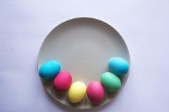 Kreis der farbigen Ostereier Eier mit Tulpen auf hölzernem Brett, Ostern-Feiertagskonzept Copyspace für Text Weißer Hintergrund Lizenzfreies Stockfoto