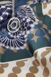 Kreisanhänger auf einem dekorativen Schal Lizenzfreie Stockfotografie