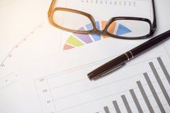 Kreisdiagramm und Balkendiagramm für Analyse von Verkäufen mit Stift und glas Stockbilder