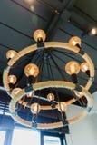 Kreisen Sie die orange Glühlampe ein und an der Decke hängen mit dunklem Hintergrund lizenzfreies stockbild