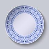 Kreisförmiges blaues Blumenmuster mit leerem Raum in der Mitte Weiße Porzellanplatte mit einem stilisierten Muster in der ethnisc Stockbild