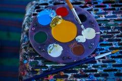 Kreismalereipalette voll der bunten Acrylfarbe, die nahe bei Malerpinsel auf befleckten Schemel mit Arbeitsbürste setzt Stockfotografie