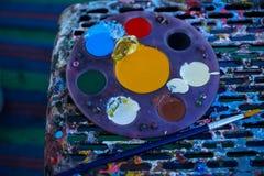 Kreismalereipalette voll der bunten Acrylfarbe, die nahe bei Malerpinsel auf befleckten Schemel mit Mattenhintergrund setzt Stockbilder