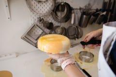 Kremeisjoghurtkuchen Mädchen kochen und stellen eine Zeichnung des Kremeises auf dem Kuchen her Gefrorenes Spiegeltüpfelchen auf  lizenzfreie stockbilder
