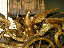 Carved and Gilt Wooden Eagle - Carriages in Kremlin Armory Museu. KREMLIN ARMORY, MOSCOW, RUSSIA - The fragment of summer carriage made in England in the 1770s Royalty Free Stock Photos