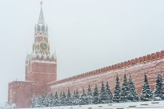 Kremlin chiming clock of the Spasskaya Tower in Moscow, Russia at wintertime during snowfall.  Stock Images