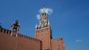 Kremlin wall, Clock on Spasskaya Tower of the Kremlin against the blue sky on a sunny summer day. Red Square in Moscow. Kremlin wall, Clock on Spasskaya Tower of stock video footage