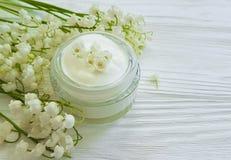 Kremowa kosmetyczna leluja doliny aromatyczny nieociosany piękno na białym drewnianym tle fotografia royalty free