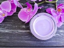Kremowego nawilżania cleanser kosmetycznego zbliżenia zbiornika gałąź świeża organicznie orchidea na menchii drewnianej zdjęcia royalty free