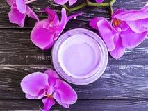 Kremowego nawilżania cleanser zbiornika gałąź kosmetyczna świeża organicznie orchidea na menchii drewnianej zdjęcia stock