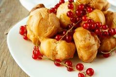 Kremowi chuchy i czerwony rodzynek na bielu talerzu Fotografia Royalty Free