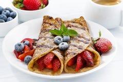 Krepps mit Beeren und Schokoladensoße zum Frühstück auf Platte Lizenzfreie Stockfotos
