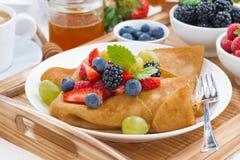 Krepps mit frischen Beeren und Honig auf einer Platte Lizenzfreie Stockfotos