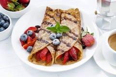 Krepps mit frischen Beeren und Schokoladensoße zum Frühstück Stockbilder