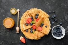 Krepps oder Blini mit Beeren und Honig lizenzfreies stockbild