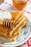 Krepps oder Blinis mit Honig zum Frühstück Lizenzfreie Stockbilder