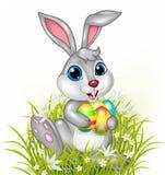 Kreskówka królik trzyma kolorowych Easter jajka ilustracja wektor
