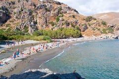 KRETA GREECE-JULY 23: Turister på den Preveli stranden på Juli 23,2014 på Kreta, Grekland Stranden av Preveli placeras 40 km södr Arkivfoto