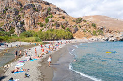 KRETA, GRIECHENLAND 23. JULI: Urlauber auf dem Preveli setzen 23,2014 im Juli auf Kreta, Griechenland auf den Strand Der Strand v Stockbilder