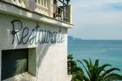 Kreta, Griekenland - Oktober 1, 2017: Overzees die restaurant met Middellandse-Zeegebied op achtergrond onder ogen zien royalty-vrije stock foto