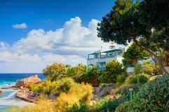 KRETA-INSEL, GRIECHENLAND, AM 1. JULI 2011: Klassisches Griechenland-Hotellandhaus auf Steinstrand unter grünen Bäumen für Touris Lizenzfreies Stockfoto
