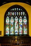 Kreuz auf Altar unter Buntglas Stockfotografie