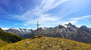Kreuz auf einem Berg vor italienischen Alpen stockfotos