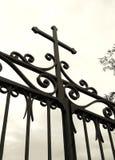 Kreuz auf Kirchegatter Stockfotografie