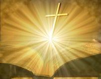 Kreuz auf offener beleuchteter Bibel Lizenzfreie Stockbilder