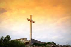 Kreuz auf Sonnenaufganghimmel Stockbild
