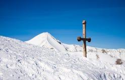 Kreuz in den schneebedeckten Bergen Lizenzfreies Stockfoto