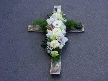 Kreuz des weißen Holzes und der Blumen Lizenzfreie Stockfotografie