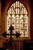 Kreuz in Front Of Blurred Stained Glass im Sepia-Ton Lizenzfreies Stockbild