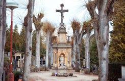Kreuz mit Statue auf Kirchhof Lizenzfreies Stockbild