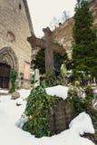 Kreuz umfasst durch Schnee auf altem Friedhof an der Kirche lizenzfreie stockbilder