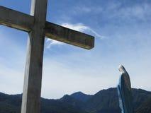 Kreuz und Jungfrau Maria vor Bergen Lizenzfreies Stockfoto
