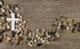 Kreuz von Steinen auf hölzernem Hintergrund für Beileid oder die Trauer Lizenzfreies Stockbild