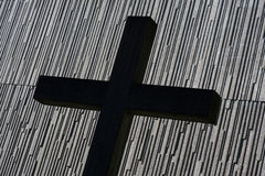 Kreuz vor moderner Kirche Stockfotos