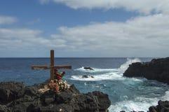 Kreuzen Sie auf clifftop und mit zusammenstoßenden Wellen unten Stockfotografie