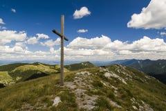 Kreuzen Sie auf die Oberseite eines Berges mit bewölktem blauem Himmel Stockfoto