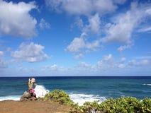 Kreuzen Sie mit Blumen auf der Klippe, die den Ozean übersieht Lizenzfreies Stockfoto